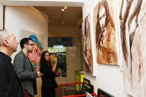 Elisa Capponi shows wine-made paintings to some art lover